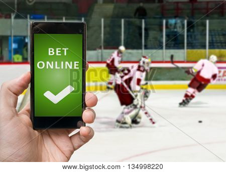 Man Is Watching Ico Hockey And Is Betting Online Via Smartphone.