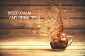 Keep calm and drink tea concept with splashing cup of tea on dark wooden background. 3D Rendering poster