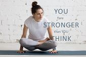 "Beautiful young woman working out in loft interior doing yoga exercise on blue mat. Motivational phrase ""You are stronger than you think"" poster"