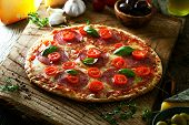 Fresh italian pizza on wood. Pizza with cheese salami and tomatoes. Fast food. Rustic pizza poster