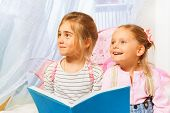 Two little girls, beautiful pixies with pink wings, reading fairy-tale before bedtime poster