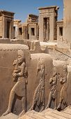 Stone frames of doorways to the palace of Darius behind embossed bas relief carvings of servants bringing gifts to the Achaemenian King at Persepolis of Shiraz. poster