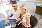 date, people, payment and finances concept - happy couple with wallet and wine glasses paying bill at restaurant poster