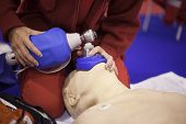 Paramedic demonstrate Cardiopulmonary resuscitation (CPR) on dummy. Artificial respiration. poster