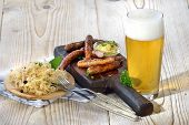Fried Bavarian sausages from Nuremberg served with sauerkraut and a lager beer poster