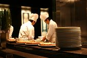 two chefs working in a busy restaurant kitchen with tasty food cooling in the foregound. poster