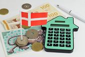 Danish notes and coins with a house shaped calculator to represent property finance. poster
