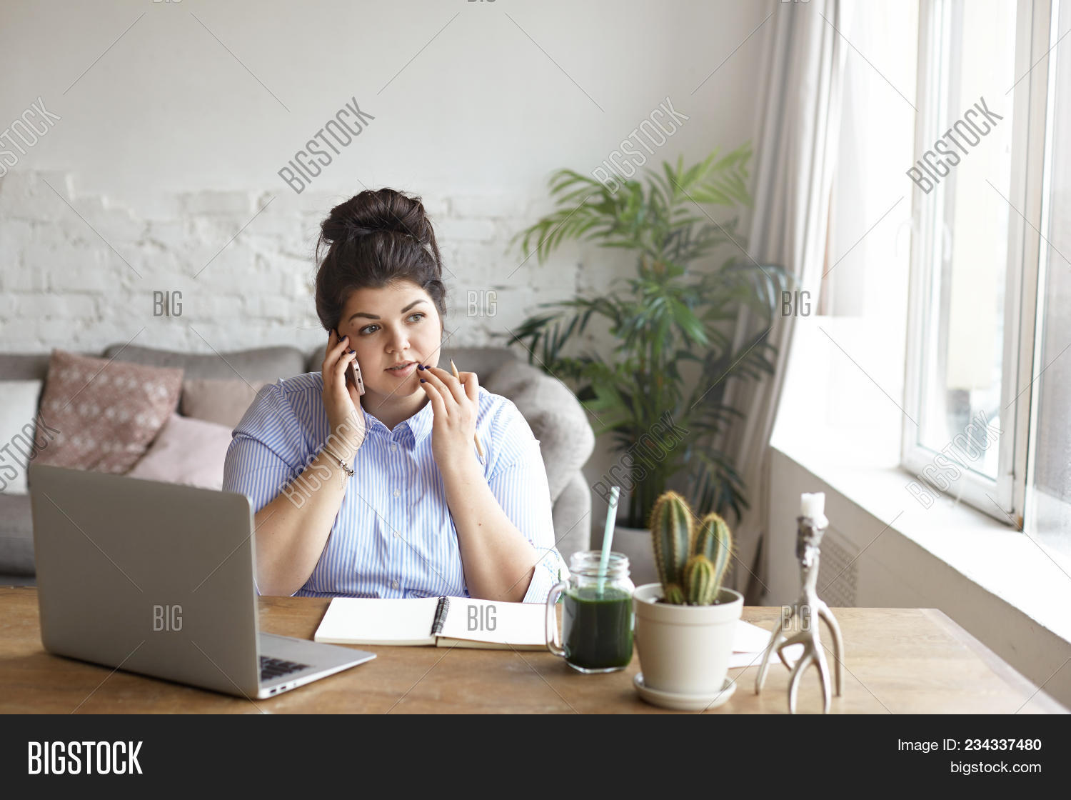 home office multitasking. Horizontal Shot Of Concentrated Chubby Young Woman With Hair Bun Multitasking At Home Office, Sittin Office I