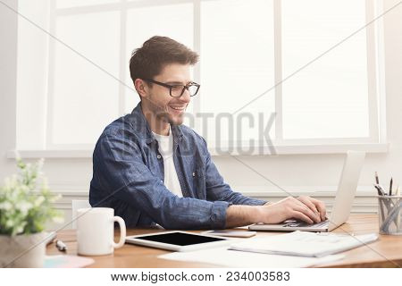 Young Smiling Man Typing On Laptop, In Modern Office. Handsome Programmer Working On Computer At Wor