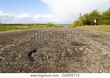 Damaged Rural Road, Cracked Asphalt Blacktop With Potholes And Patches. Poor Quality Of Road Repair