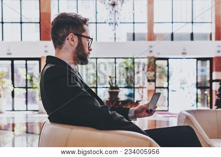 Side View Of A Bearded Young Successful Man Employer In A Formal Suit Sitting In A Beige Armchair In