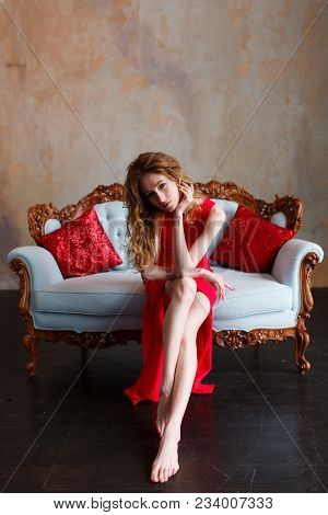 Elegant Sensual Young Redhair Woman In Red Dress Sitting On Classic Sofa And Looking At Camera. Loft