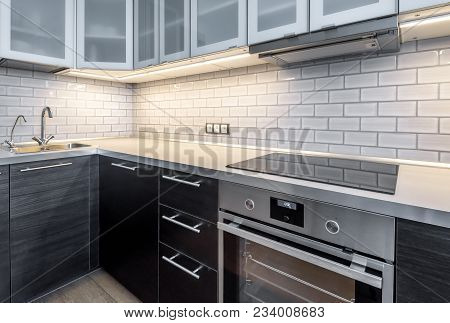Interior Of Kitchen With Lighting. Modern Kitchen With Electric Stove And Oven. Black Induction Cook
