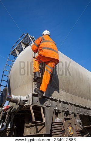 A Railway Maintenance Worker Wearing Hi Viz Clothing Climbing A Ladder Onto A Rail Tanker To Inspect