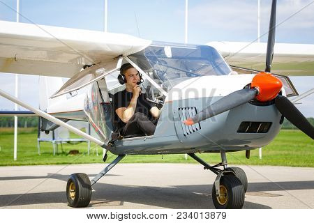 Handsome Teenage Man Sitting In Small Plane Cockpit. Young Pilot With Headset On. Outdoor Shot.