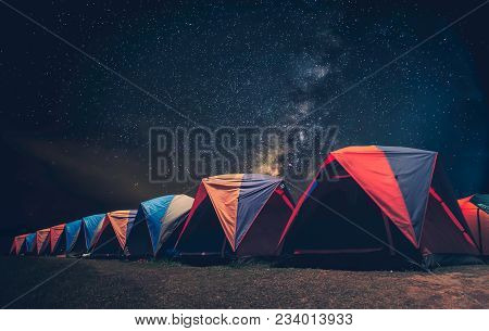 Tourist Near His Camp Tent At Night Under A Sky Full Of Stars. Orange Illuminated Tent