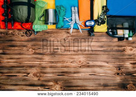 Top View Of Equipment For Hiking And Travel On Gray Background With Copy Space . Items Include Trekk