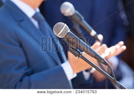 Microphone In The Focus Against Blurred Speaker. News Conference. Public Relations - Pr.