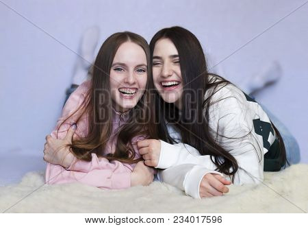 Portrait Of Two Sisters Lying On The Floor Smiling. Concept Of: Family, Sisters, Home And Happiness