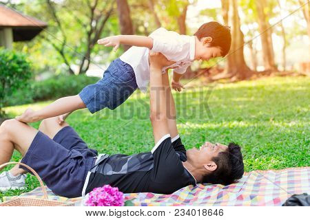 Good Daddy And Son Concept: Father Play Flying With His Boy In The Park When Picnic On Holiday