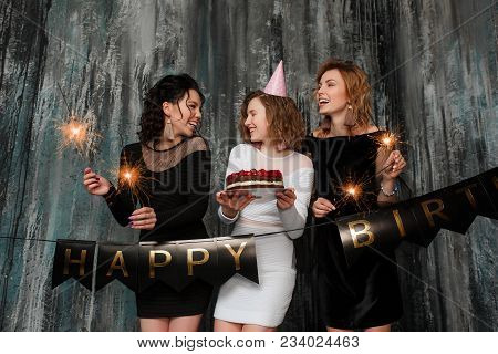 Three Women Celebrating Birthday Party Hard. Portrait Of Joyful Friends Toasting With Glasses Of Cha