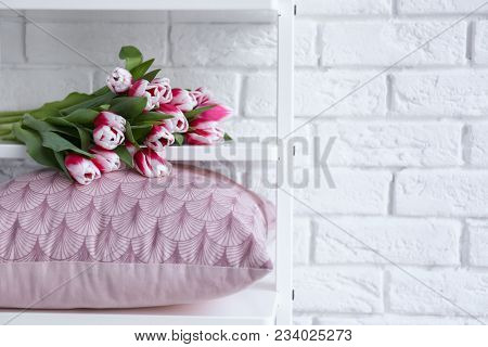 Shelving with pillow and flowers near brick wall