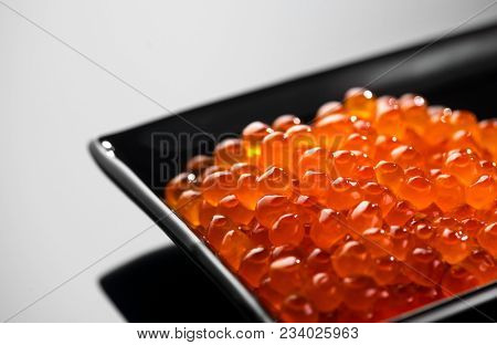 Red Caviar in a black plate. Caviar in bowl over black background. Close-up salmon caviar. Delicatessen. Gourmet food. Texture of caviar. Seafood.