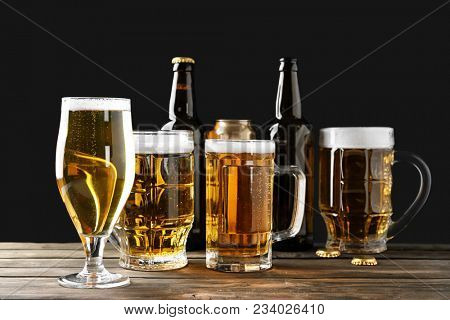 Different glassware with beer on wooden table against black background
