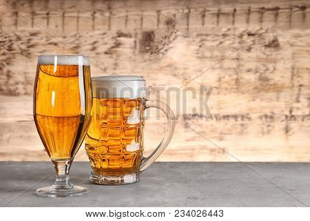 Glass and mug with fresh beer on wooden background