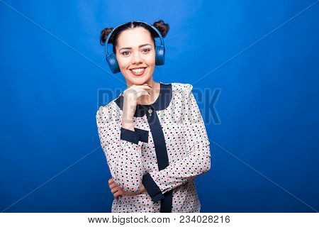 Smilng Woman Looking At The Camera And Listening Music On Blue Background In Studio Photo