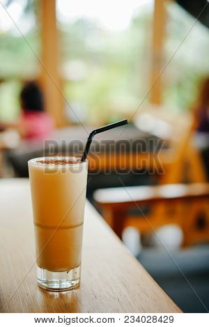 Cold Cappuccino With Cinnamon And A Straw On The Table In A Cafe. Delicious And Invigorating Drink I