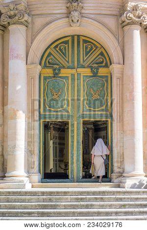 Scicli, Italy - June 8, 2012: Sicily Island, A Nun Entering In San Giovanni Evangelista Church.