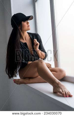 Sexy Long-haired Brunette Wearing Black Leather Jacket And Baseball Cap Sitting On The Window Sill