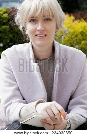 Young Attractive Business Woman With Long Curly Hair Holds A Job Interview. Young Beautiful Woman Jo