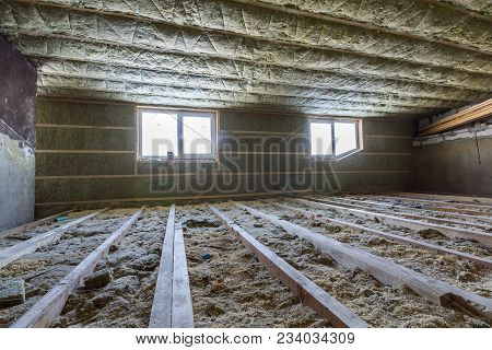 House Attic Under Construction. Mansard Walls And Ceiling Insulation With Rock Wool. Fiberglass Insu