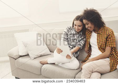 Two Happy Female Friends Using Digital Tablet. Laughing Women Browsing Portable Computer, Having Fun