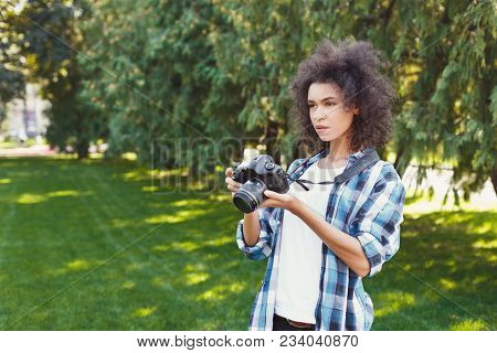 Attractive Young African-american Woman Photographing Outdoors, Watching Pictures On Professional Ca