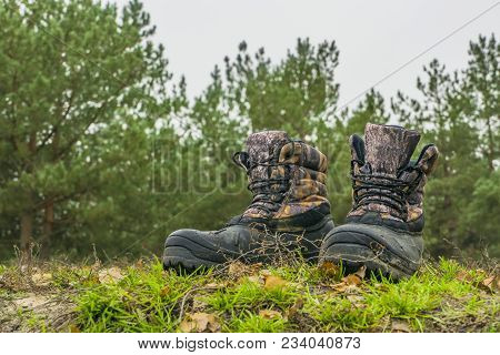 A Pair Of Worn Hiking Boots On Natural Background. Dirty Boots For Hiking, Fishing, Traveling.