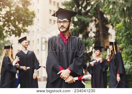 Young Serious Male On His Graduation Day Showing Standing With Multiethnic Group Of Friends. Educati