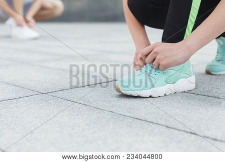 Unrecognizable Man And Woman Tying Shoelaces On Sneakers Before Running, Getting Ready For Jogging I