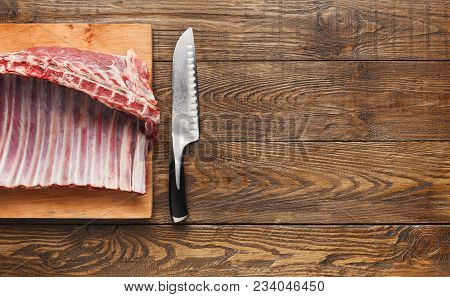 Raw Cut Rack Of Lamb. Fresh Meat On Wooden Board With Knife On Kitchen Table Background. Organic Ing