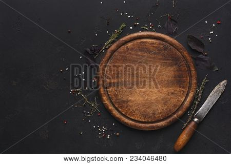 Wooden Cutting Board With Knife And Spices On Dark Background. Rustic Catering Platter For Cutting P