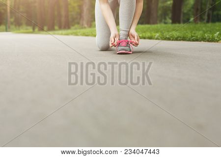 Unrecognizable Woman Tying Shoes Laces Before Running, Getting Ready For Jogging In Park, Copy Space
