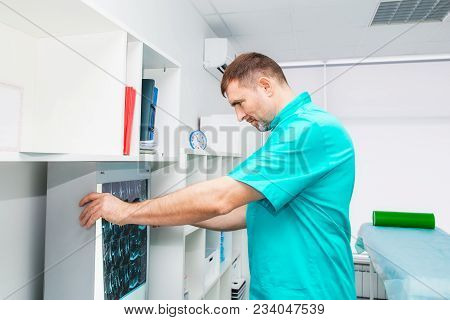 Male doctor looking at x-ray image of cervical spine in his office. Osteopathy, chiropractic, physiotherapy. Healthcare, roentgen, people and medicine concept. Selective focus, space for text poster