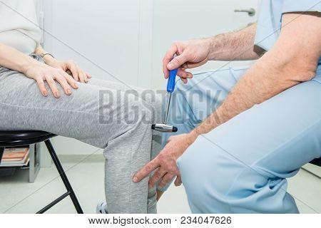 The Neurologist Testing Knee Reflex On A Female Patient Using A Hammer. Neurological Physical Examin