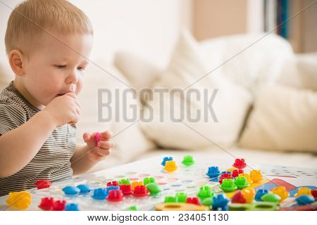 Cute Preschooler Child Boy Plays With Mosaic At Home. A Blond Little Toddler Playing In Kid's Room.