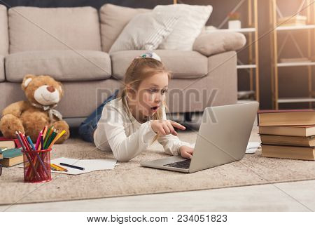 Shocked Little Casual Girl Watching Movie. Surprised Female Kid Lying On The Floor, Home Alone, Watc