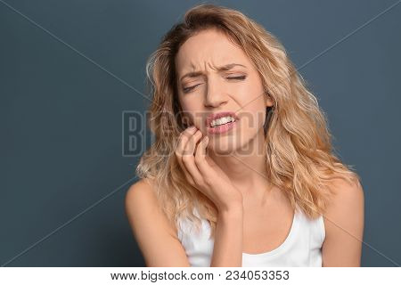 Young Woman Suffering From Toothache On Color Background