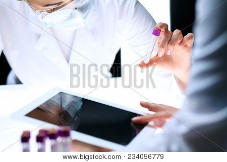 Closeup Of Scientific Research Team With Clear Solution In Laboratory. Blonde Female Chemist Holds T