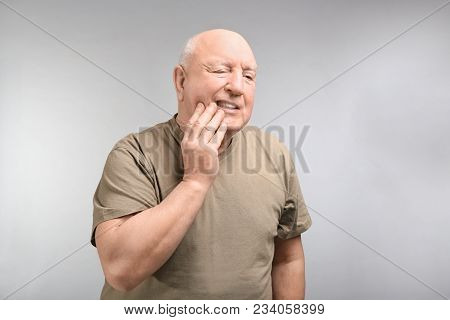 Senior man suffering from toothache on light background. Enduring pain poster